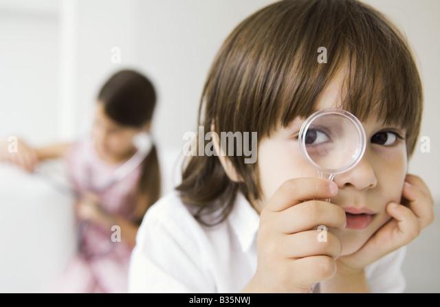 Kleiner Junge Blick durch die Lupe in die Kamera Stockbild