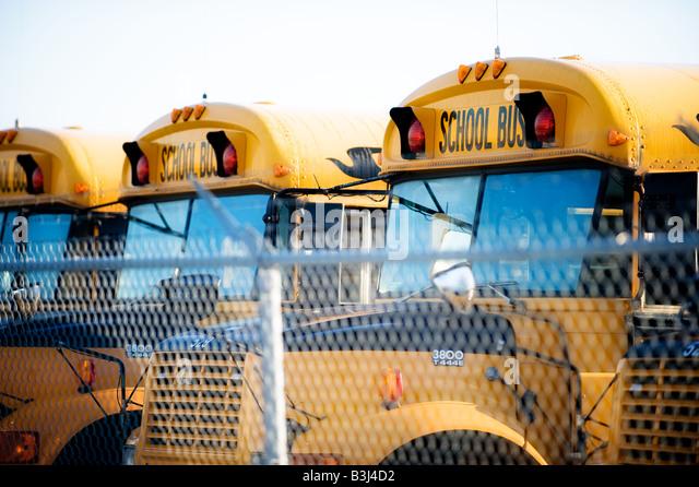 Mehrere Busse aufgereiht in einem Depot für die Schule-Saison bereit. Stockbild