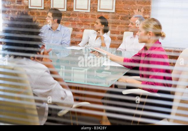 Fünf Geschäftsleute im Sitzungssaal durch Fenster Stockbild