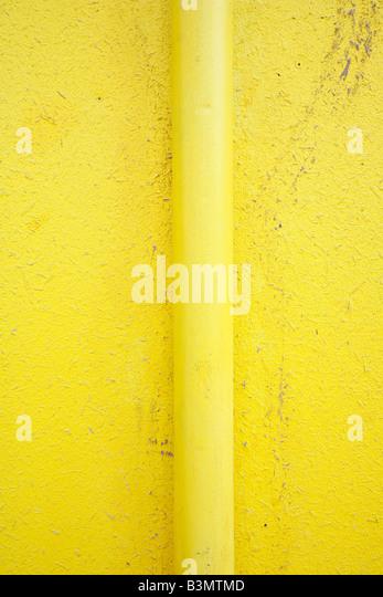 Rohr auf gelbe Wand Stockbild