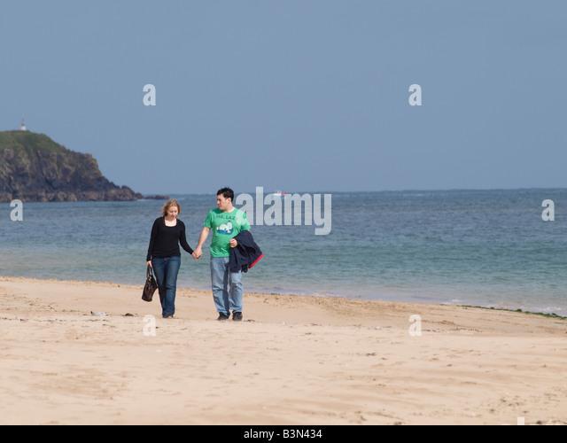 30er Jahre Paare, die an einem Sandstrand, Hand in Hand. Stockbild