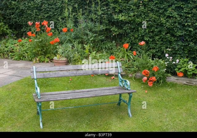 leere Schmiedeeisen Bank mit Holzlatten befindet sich im Garten Stockbild