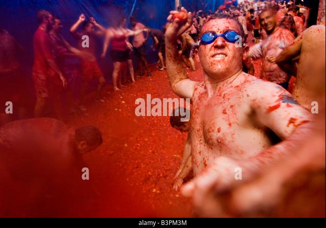 Mann trägt Swimming goggles wirft eine Tomate auf La Tomatina Essen Festival kämpfen. Bunol. Valencia, Stockbild