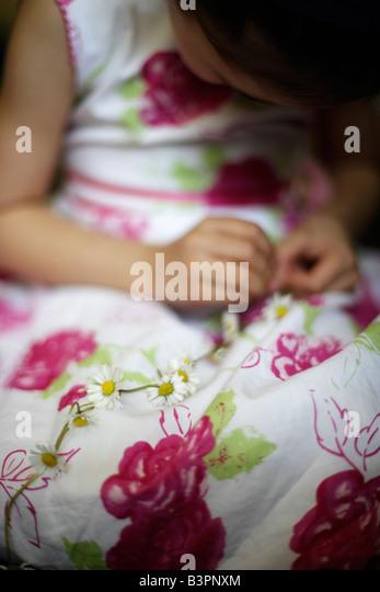 Fünf Jahre altes Mädchen macht Daisy-chain Stockbild