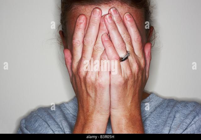 verheiratete Frau, die ihre Augen mit den Händen bedecken Stockbild