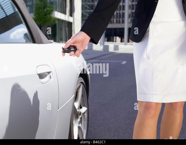 Deutschland, Baden-Württemberg, Stuttgart, weibliche Person bei Sportwagen mit Fernbedienung Schlüssel, Stockbild