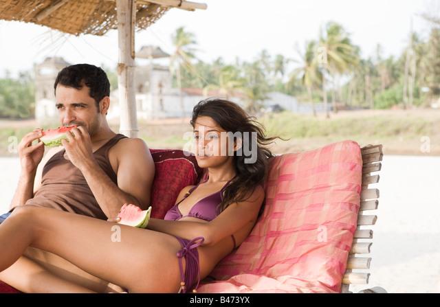 Paar in Sonnenliegen mit Wassermelone Scheiben Stockbild