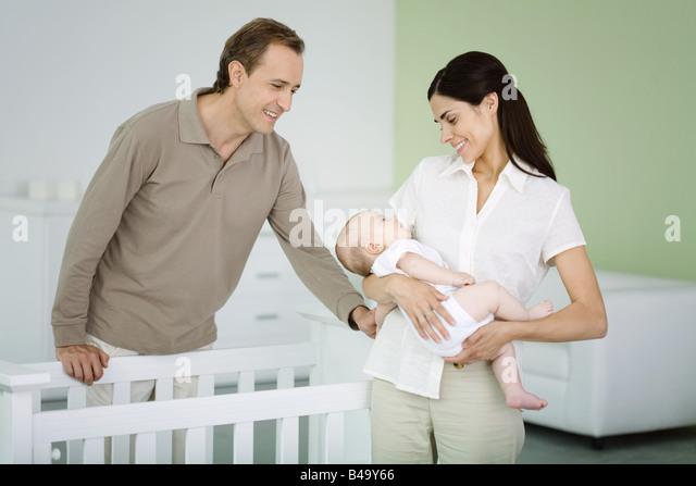 Eltern stehen in Kindergarten, Frau Holding schlafendes baby Stockbild