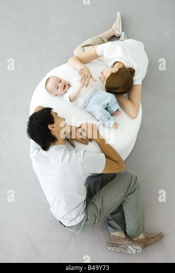 Eltern und Baby entspannend auf osmanischen, Baby halten die Hand der Mutter, Draufsicht Stockbild