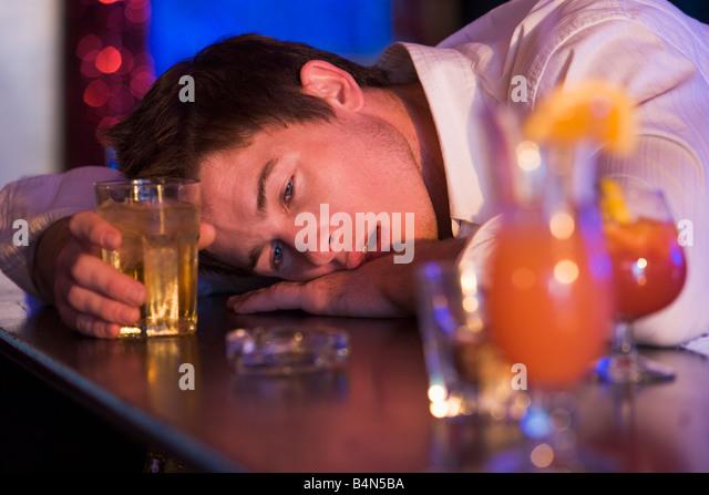 Jungen Mann betrunken übergebenen in Bar Stockbild