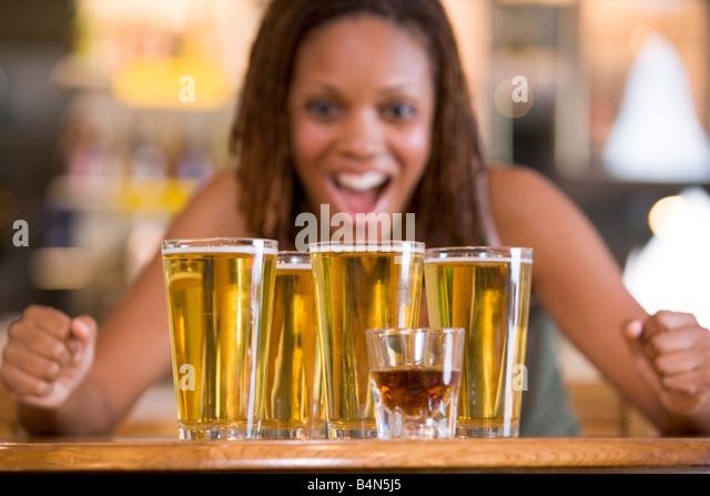 Frau posiert mit mehreren Biergläser Stockbild