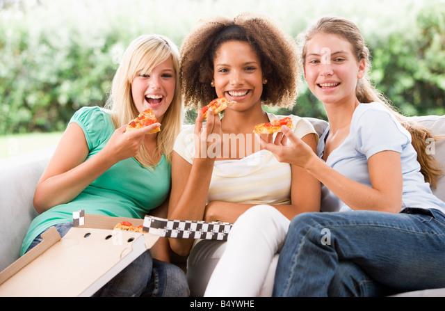 Teenager-Mädchen auf der Couch sitzen und essen Pizza Stockbild