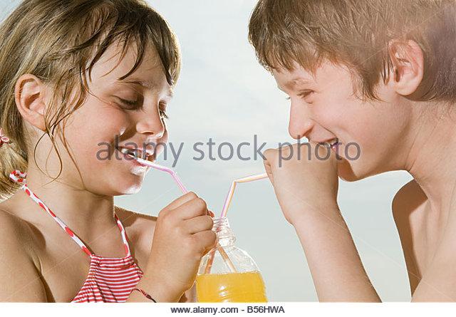 Mädchen und jungen teilen Getränk - Stock-Bilder