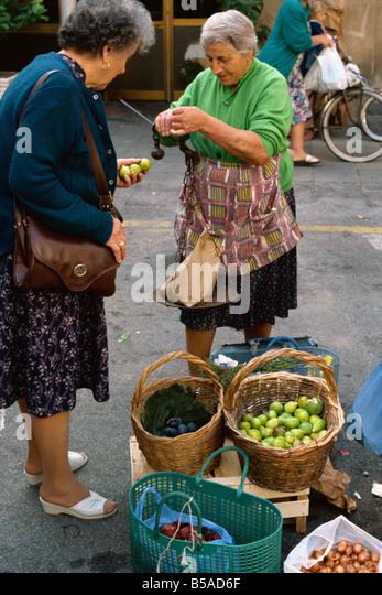 Frau verkaufen Feigen mit einem altmodischen Gleichgewicht auf dem Markt von Pescia in Toskana Italien M Newton Stockbild