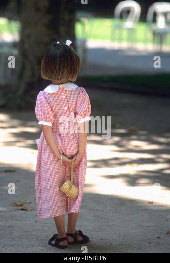 Kleines Mädchen in einem hübschen roten aufgegebenes Kleid und Schleife im Haar in einem park Stockbild
