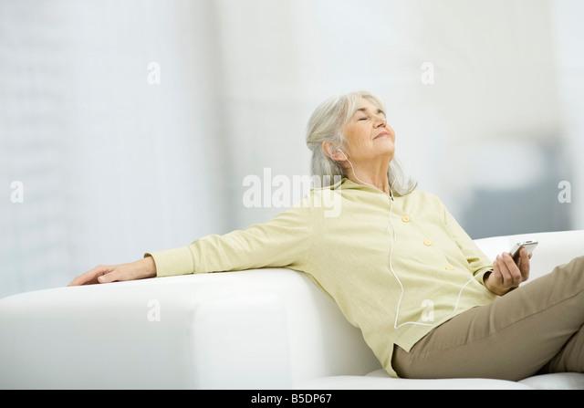Ältere Frau Musik anhören, auf Couch sitzen mit geschlossenen Augen Stockbild