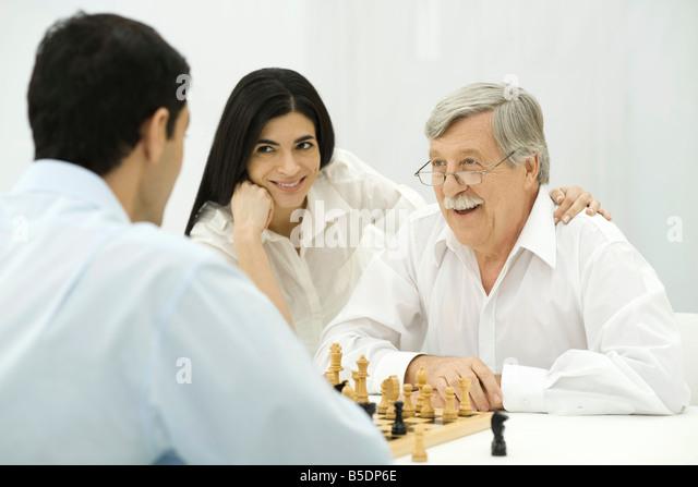 Leute spielen Schach, Frau sitzt mit der Hand auf die Schulter des Mannes senior Stockbild