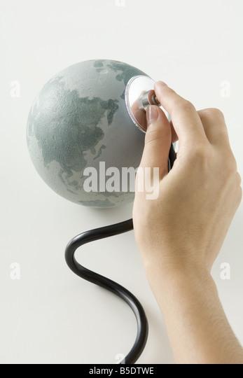 Hand mit Stethoskop auf kleine Weltkugel Stockbild