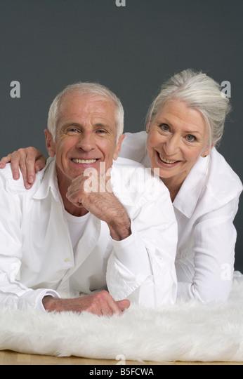 Älteres paar liegen auf einem Fell Teppich Stockbild