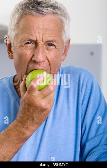Ältere Mann isst einen Apfel Stockbild