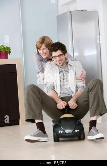 Junge Paare, die Spaß zu Hause Mann treibende Spielzeugauto Stockbild