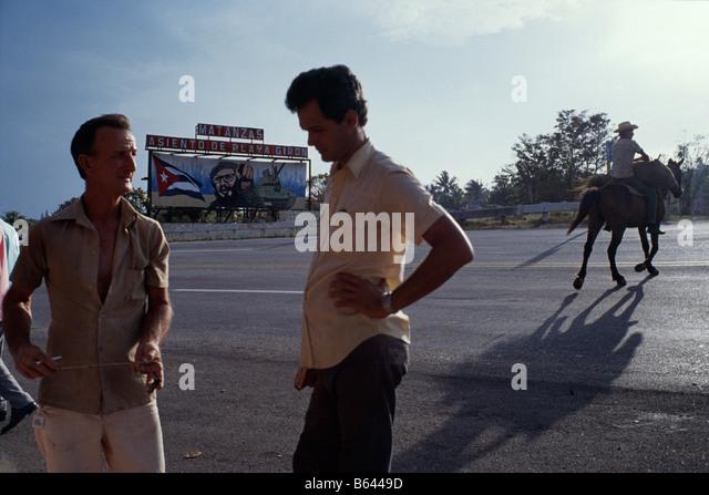 Männer und Pferde am Straßenrand neben einer Plakatwand, die Darstellung der kubanische Präsident Stockbild