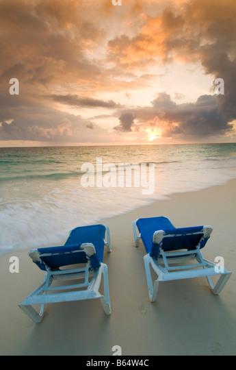 Karibik Dominikanische Republik paar Sonnenliegen am Strand bei Sonnenaufgang vor Resort all inclusive Stockbild