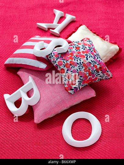 Kissen und Buchstaben auf einem Teppich - Stock-Bilder
