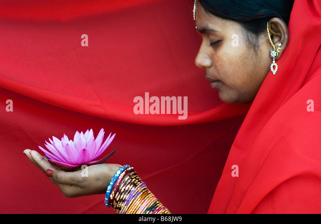 Indische Frau bietet eine Nymphaea tropische Seerose Blume in einem roten sari Stockbild