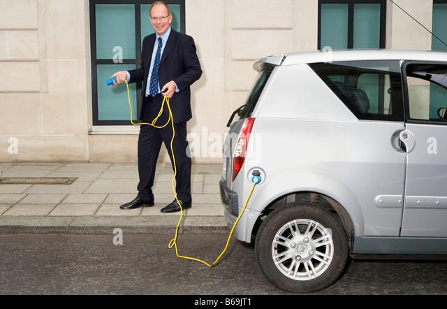 Mann hält Kabel für Elektro-Auto Stockbild