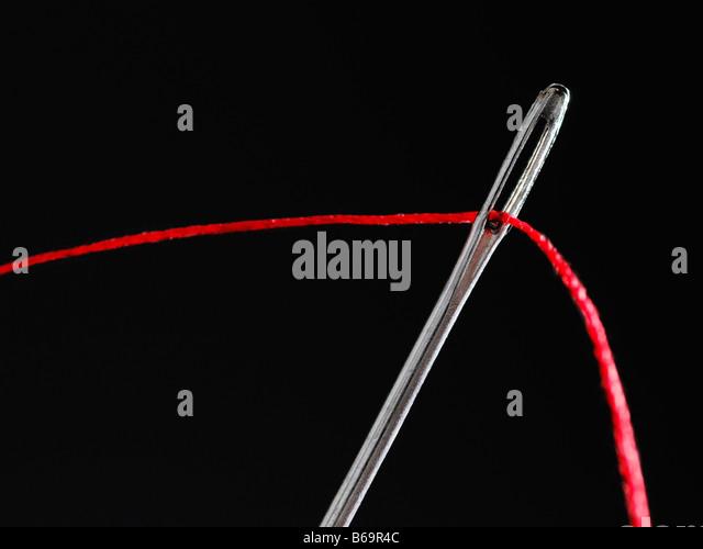 Faden durch ein Nadelöhr hautnah Stockbild