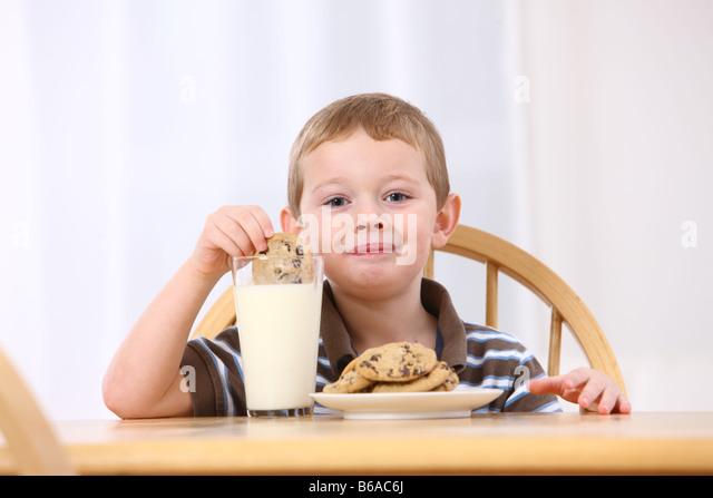 Jungen setzen Cookies in Milch Stockbild