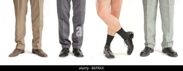 Vier Unternehmer stehen in einer Zeile ohne Hosen, Detail der Beine Stockbild