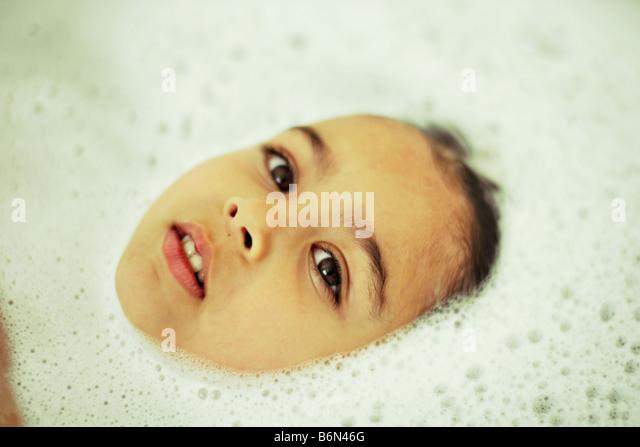 Fünf Jahre altes Mädchen im Schaumbad Stockbild
