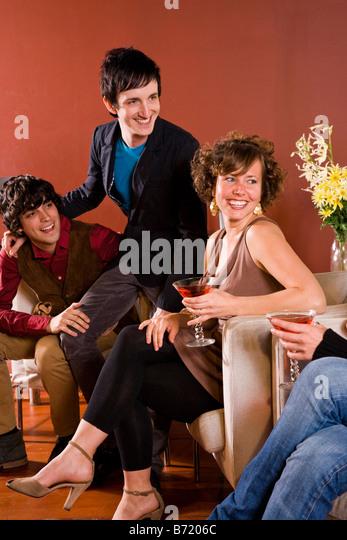 Stilvolle junge Erwachsene im modernen Wohnzimmer sitzen, lachen Stockbild