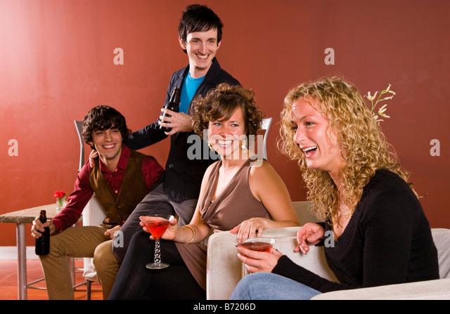 Freunde hängen in modernen Wohnzimmer tranken und lachten - Stock-Bilder