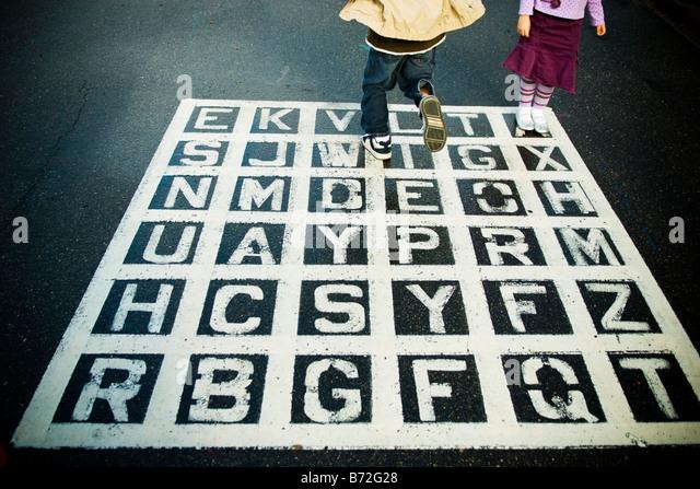 Kinder spielen auf einem Asphalt-Alphabet-Spiel auf dem Schulhof. Stockbild