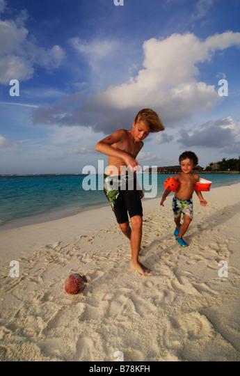 Kinder spielen Fußball am Strand des Laguna Resort, Malediven, Indischer Ozean Stockbild