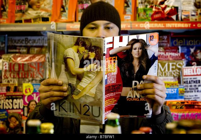 Ein Mann liest eine Zeitschrift FHM Stockbild