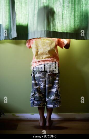 Sechs Jahre alter Junge blickt Fenster hinter Gardinen Stockbild
