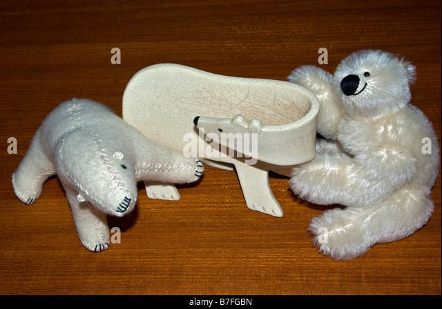 Keramik und gefüllte Spielzeug Eisbären auf Teakholz-Tisch Stockbild