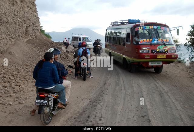 Abschnitt des Trans Flores Highway in der Nähe von Ende Gunung Mej Vulkan im Hintergrund Stockbild