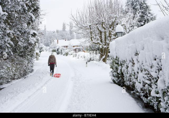 Mädchen mit Schlitten in Wohnstraße im Winter. Surrey, UK Stockbild