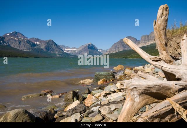 Blick über See und Many Glacier St. Marien mit einem toten Baumstamm als Vordergrund Interesse Stockbild