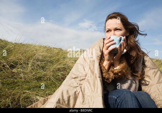 Frau im Freien mit Decke und Getränk Stockbild