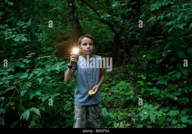 Junge mit Taschenlampe im Wald Stockbild