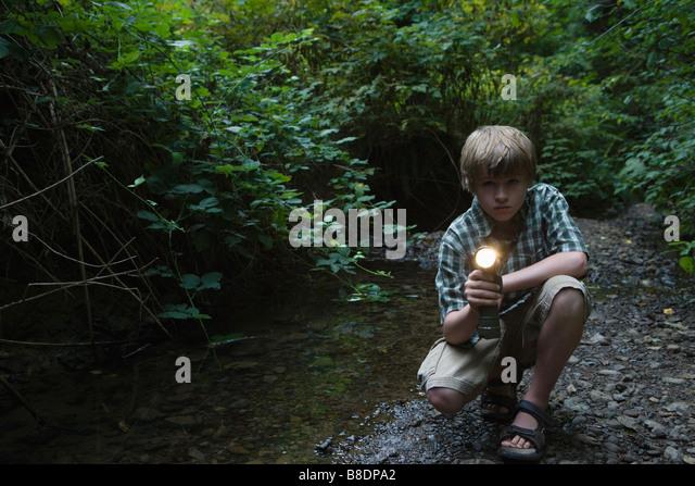 Junge mit Fackel durch Fluss Stockbild