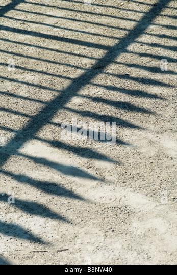 Schatten des schmiedeeisernen Zaun auf Schotter Stockbild