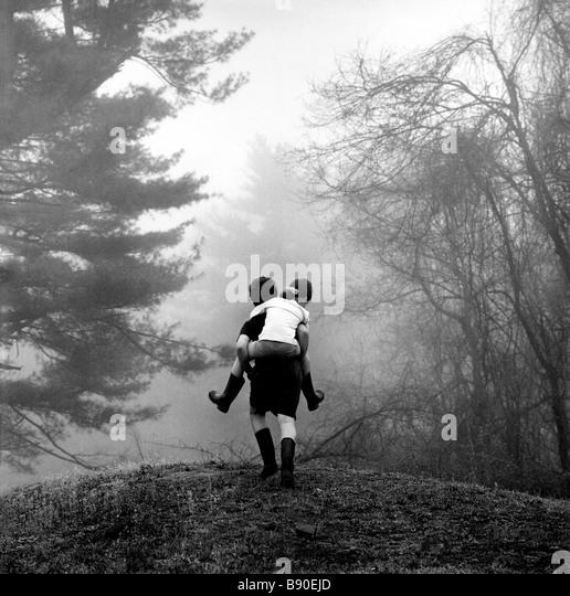 FL2608, NICK KELSH; Huckepack junge Mädchen durch Wald Stockbild