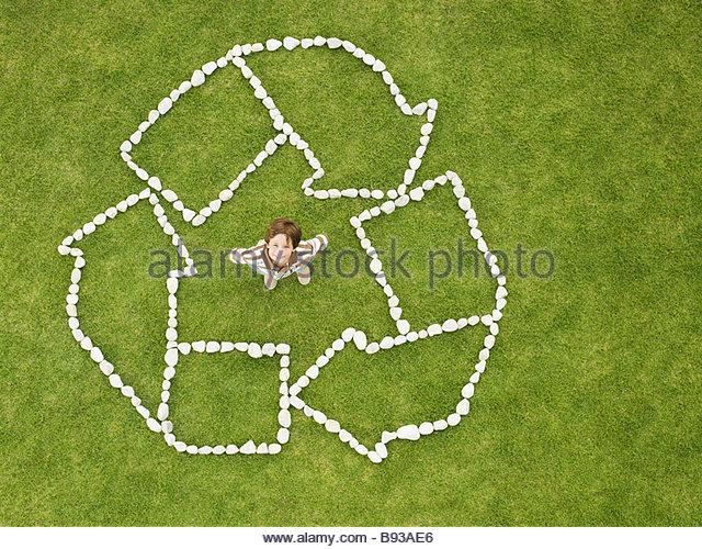 Junge in recycling-Zeichen stehen gemacht von Felsen Stockbild